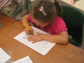 Óvódás kislány tenyerel egy feladatlapon, jobb kezében sárga zsírkréta.