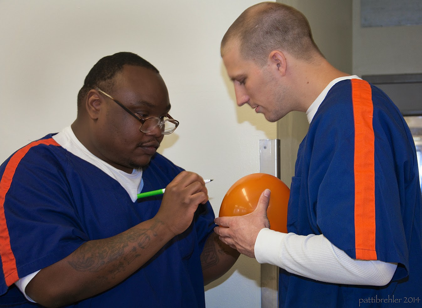 An african american man dressed in the blue prison uniform draws on an orange balloon with a green marker. He is on the left facing another man dressed in the prison uniform on the right. The man on the right is holding the orang e balloon.and looking down at it.