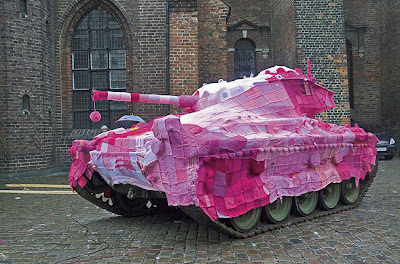 army tank covered in a large afghan crocheted in shades of pink