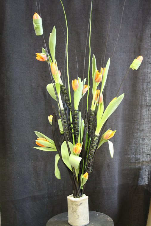 Dried leaves and twigs set into the base and decorated with tulips