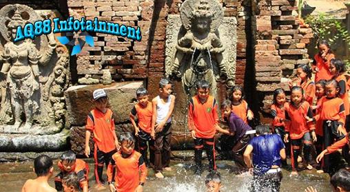 Sekelompok anak sepulang sekolah kegirangan bermain air di sebuah kolam di depan arca , sekujur tubuh dan seragam yang masih mereka kenakan nampak kuyup.