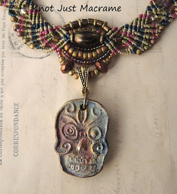 Raku skull pendant on knotted necklace