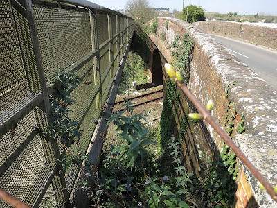 View between road bridge and footbridge, showing railway below.