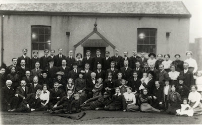 A large group of smartly dressed 1900 ish men and women sat in a formal group with a soldier lying casually at the front.  A small chapel behind with a window on either side of a central porch.