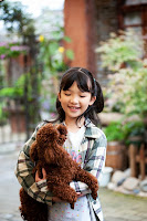 A young girl holds her pet poodle