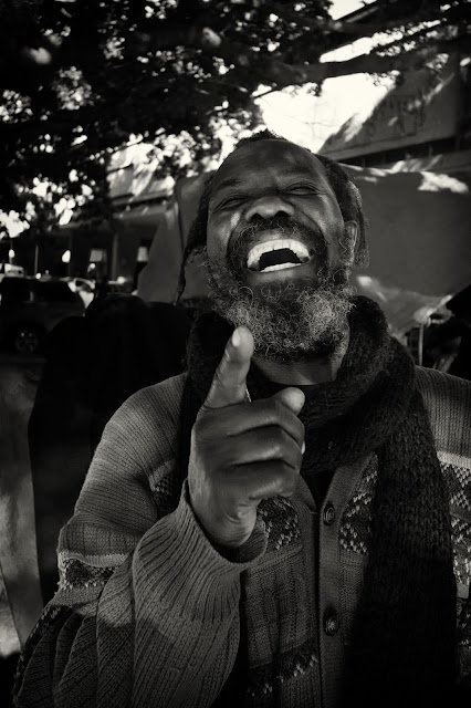 A bearded man laughs with eyes closed and points at the camera