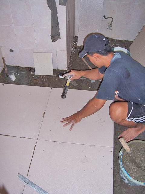 Meratakan ketinggian keramik dengan diketuk-ketuk menggunakan gagang