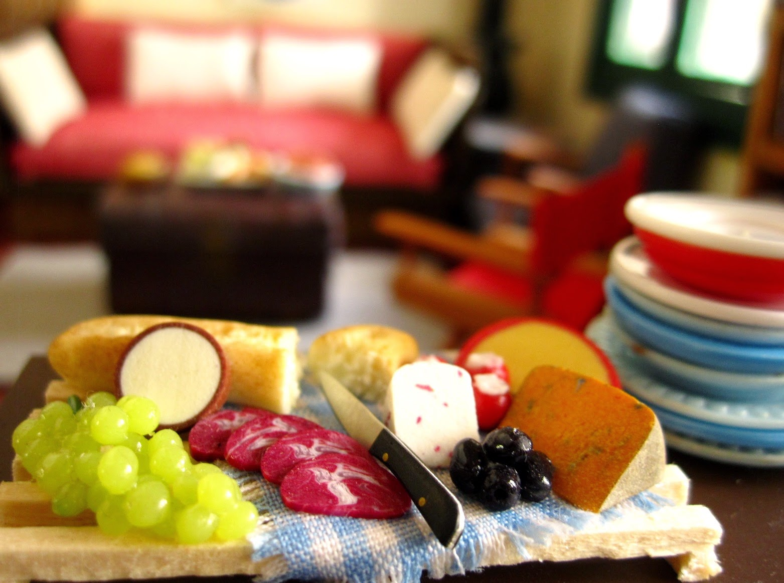 Miniature dolls' house cheese platter on a table next to a pile of plates, In the background is a seating area.