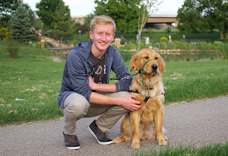 Ian smiles kneeling next to a Golden Retriever guide dog puppy.