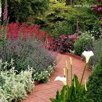 Vereda de ladrillos colorados en un jardín florecido