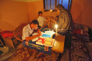 Fayza Al-Louh, 48, watches her son Zaid, 19, study during power outage in Beit Lahiya, northern Gaza Strip