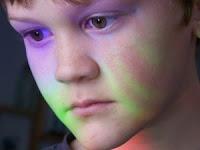 Menino com rosto colorido com as cores do monitor