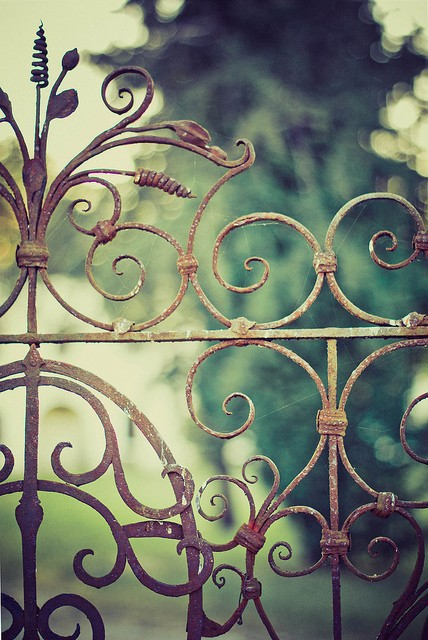 An Old Iron Headboard Serves As A Garden Gate