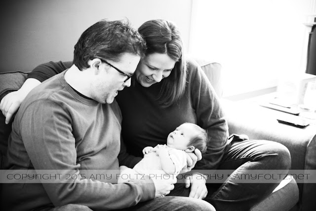 black and white lifestyle photo of newborn with parents