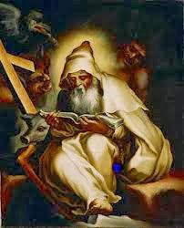 El Santo vestido de monje sentado leyendo, demonios detras y una cruz y un cerdito a su lado