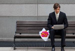 Finding The Online Dating Sweet Spot - man using laptop on a garden bench