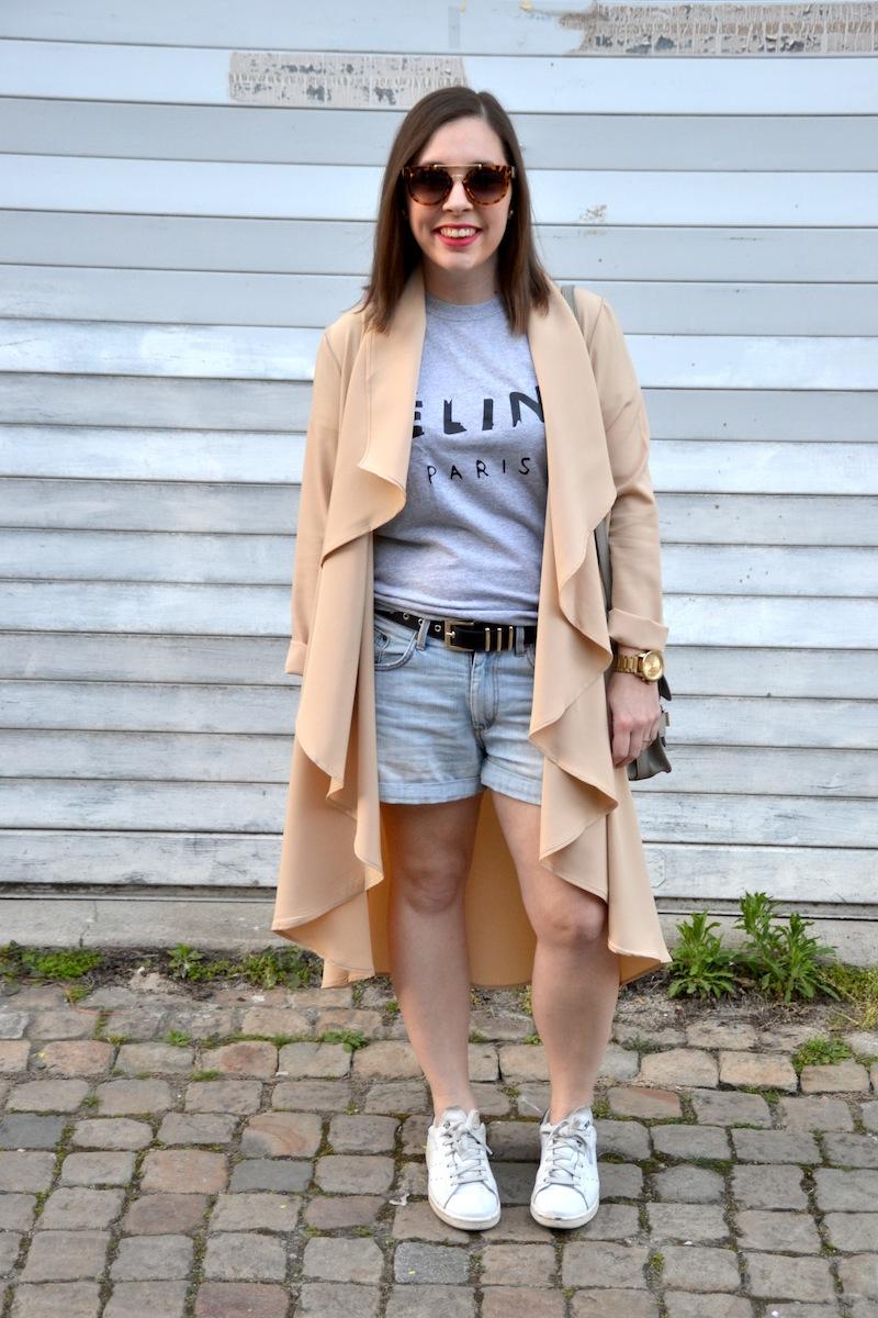 trench asymétrique long beige, top céline gris et short en jean et lunette de soleil écaille de l'usine à lunettes
