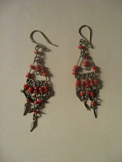 Delicate bronze-color or antiqued metal dangle earrings. From the ear wire they form an inverted triangle with three red-orange beads on each side and a stem dangling in the middle, with two beads on it. Then there is a chandelier effect of a row of metal dangles, then two rows of beads, then a final tapered row of metal dangles with beads leading to three delicate diamond-shaped points at the bottom, with the one in the middle longer than the ones on either side.