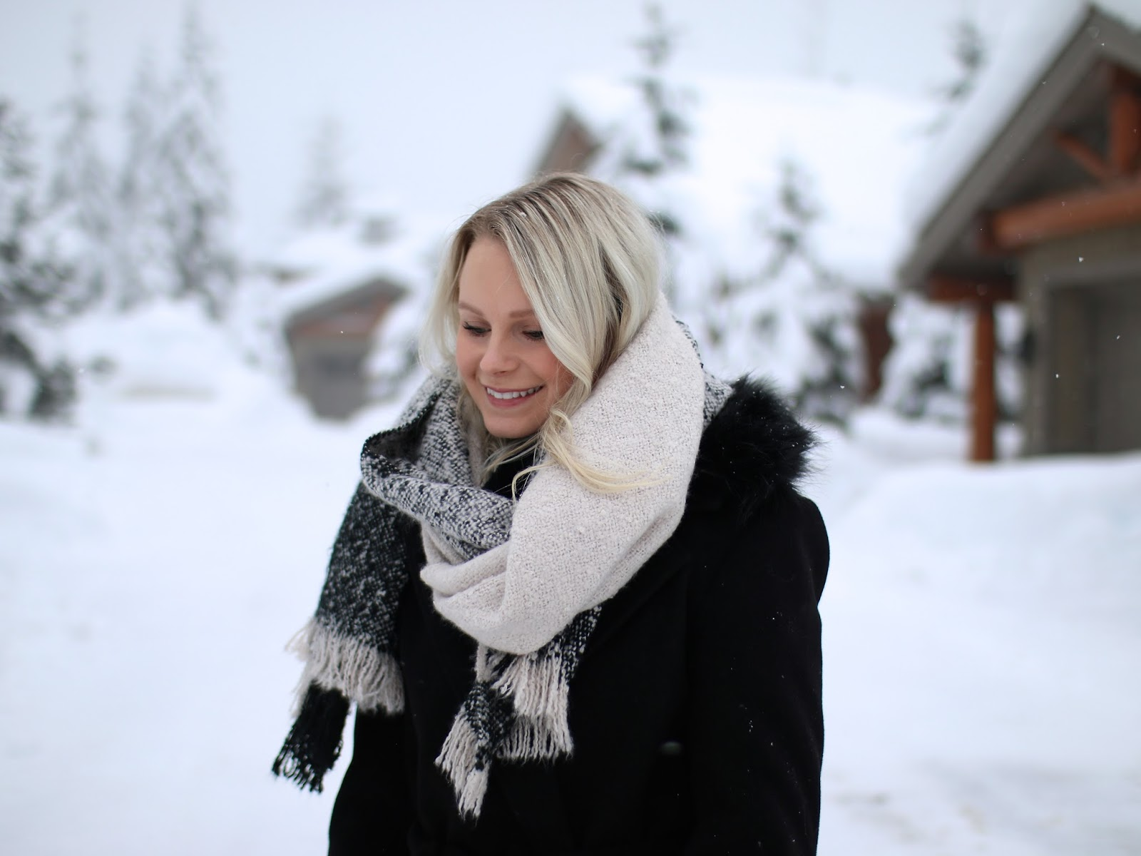 a blonde women models how to style over a beige over sized scarf standing in the snow
