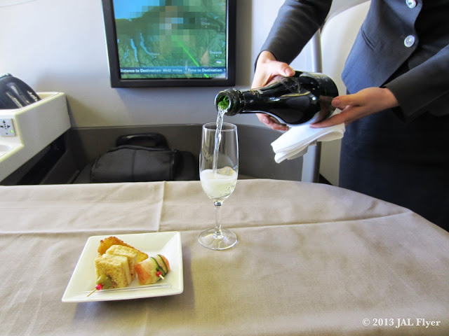 JAL First Class trip report on JL005: JAL senior cabin attendant pouring Champagne SALON 1999