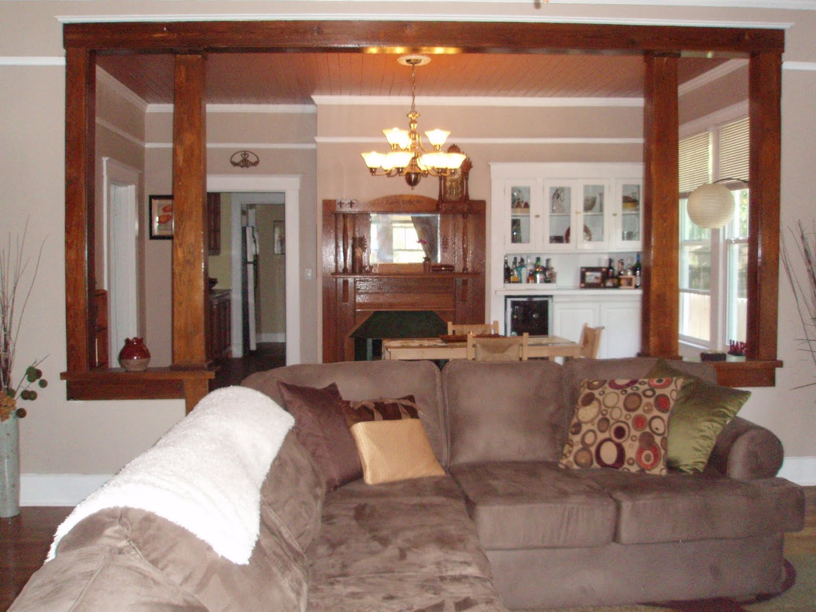 Spacious living room with large windows and original wood pillar  title=