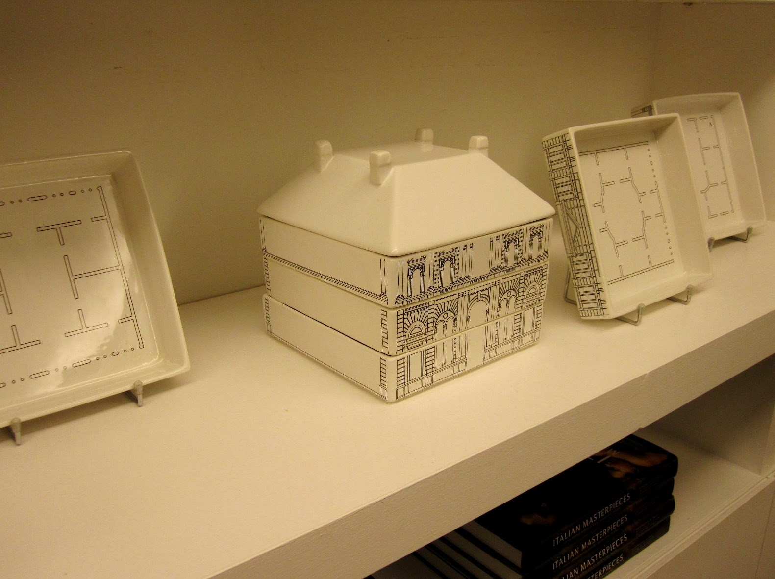 Porcelain stacking plates in the shape of a house on display in a shop.