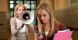 A girl using her cell phone in the hall way at school and a principal or teacher yelling at her with a bullhorn about using her cell phone