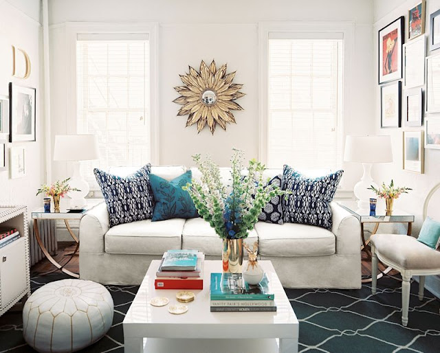 Living room with white sofa, navy fence print rug, a white coffee table, a white Moroccan pouf, large windows and a mirror in the shape of a sun
