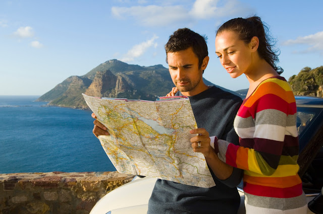 Couple on an adventure looking at a map with the ocean in the background.