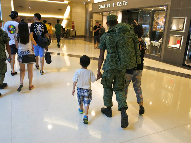 kid holding soldier's hand