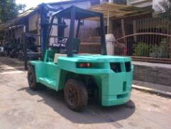 Forklift bekas Mitsubishi berwarna hijau parkir di depan rumah