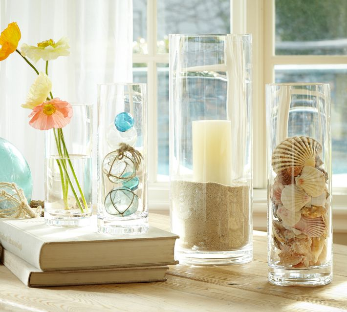 Sand fills a cylinder vase holding a pillar candle