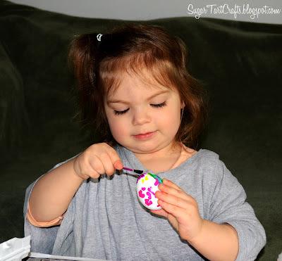 little girl painting eggs