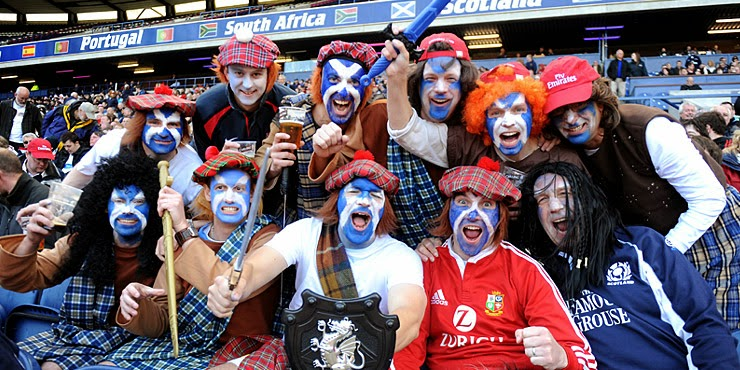 Scotland rugby fans with saltire face paint and tartan kilts and bonnets