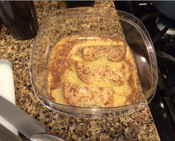 Clear bowl containing French Toast egg mixture, 3 slices of toasts soaking in mixture.