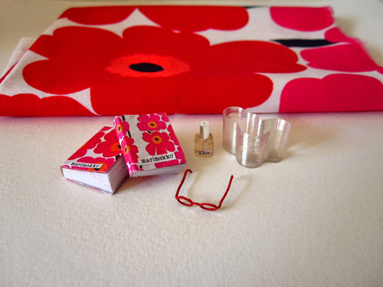 Miniature Marimekko books, red reading glasses, Dior perfume bottle and  Aalto vase arranged in front of a piece of full-sized Unikko fabric.