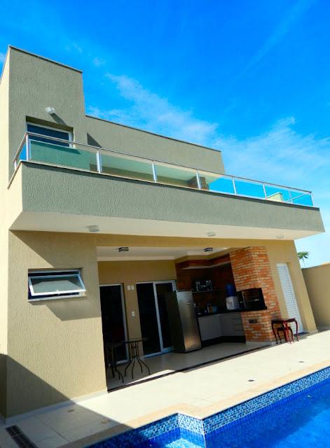 A partir da piscina, a visão da elevação posterior da residência, com varanda gourmet abraçada por um lavabo e um depósito, diante da sala de jantar e cozinha.
