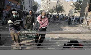 Egyptian protesters carry a container of rocks