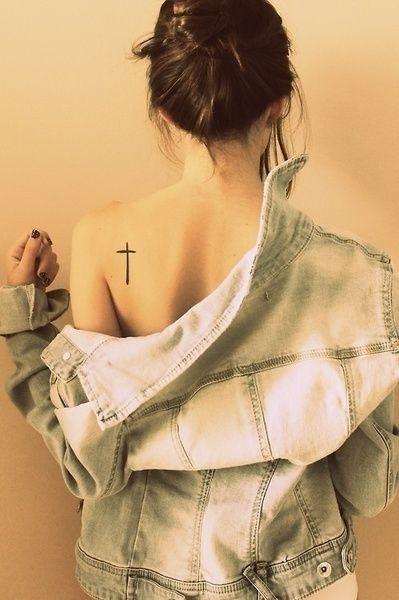 Chica de espaldas usando una chaqueta de mezclilla mostrando su tatuaje en forma de cruz sobre su omóplato derecho
