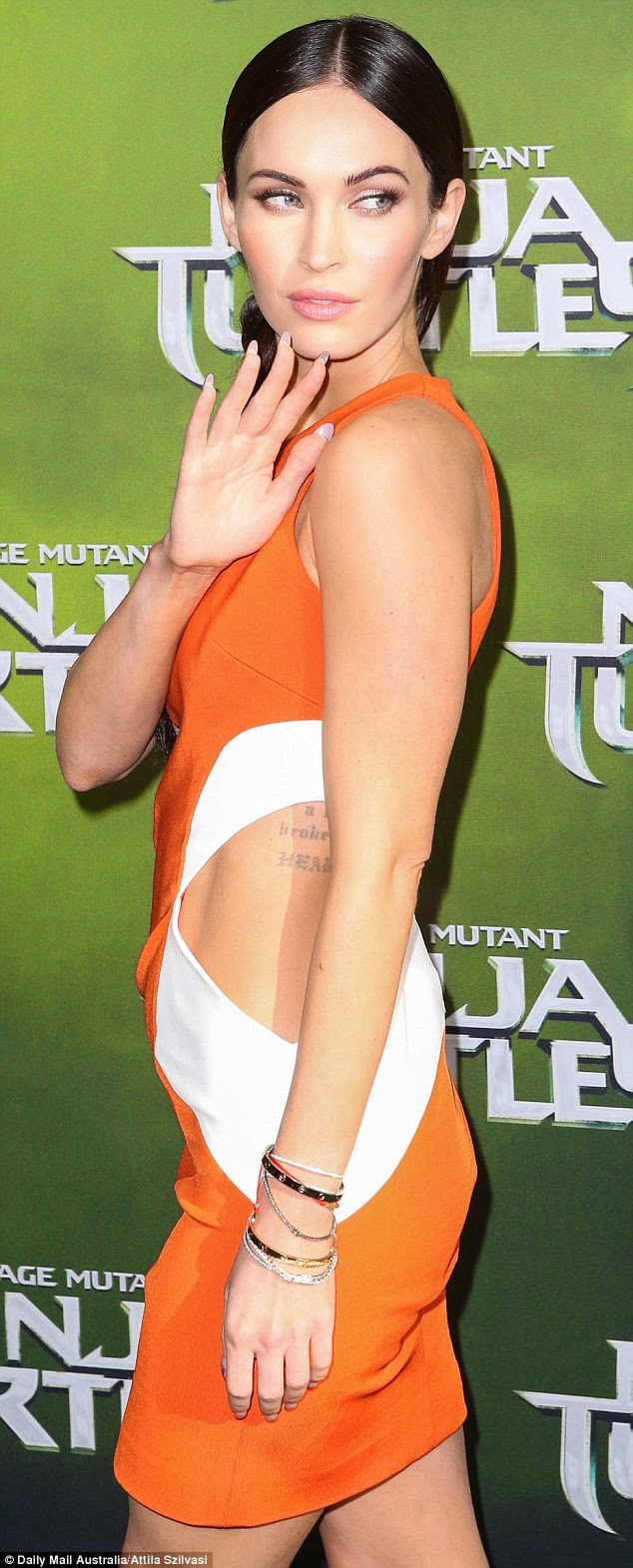 Megan Fox shows off tattoos in an orange cutout dress at the 'Teenage Mutant Ninja Turtles' Sydney premiere