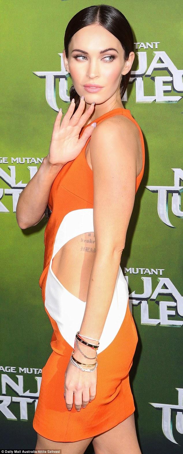 Megan Fox shows off tattoos in an orange cutout dress at the 'Teenage Mutant Ninja Turtles' Sydney premiere