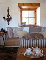 Salon farmy urządzony w rustykalnym stylu: rustykalna sofa, pobielona ściana