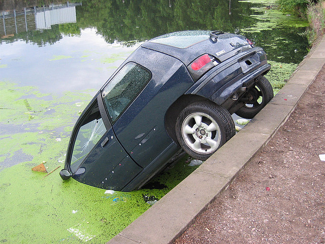 A small car half submerged in a pond