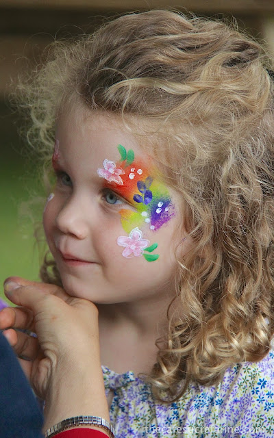 Lilly with her face painted with a rainbow and colorful flowers.