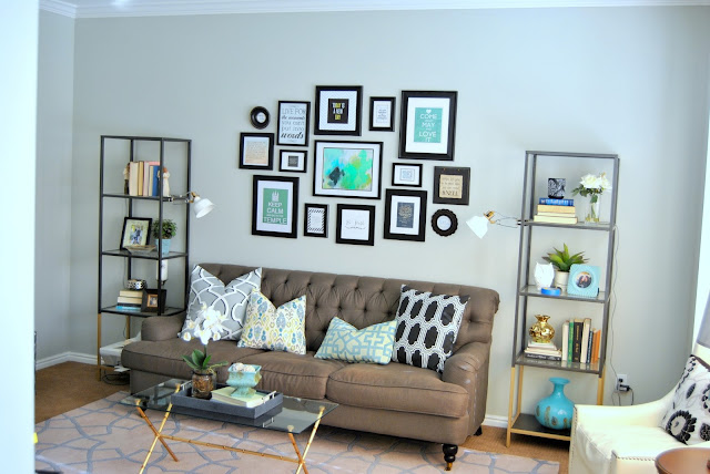aloof gray, living room, sherwin williams, gray walls, gray paint, gallery wall, black frames, black gallery wall, vittsjo, shelves, book case, staged book case, gray sofa, tufted sofa, gold coffee table, white chair, nailhead, area rug, blue, turquoise