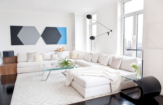 Living room with a large white sectional, glossy dark floor, glass coffee table and modern art