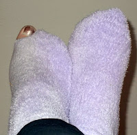 Picture of feet with purple socks with a hole in the toe.