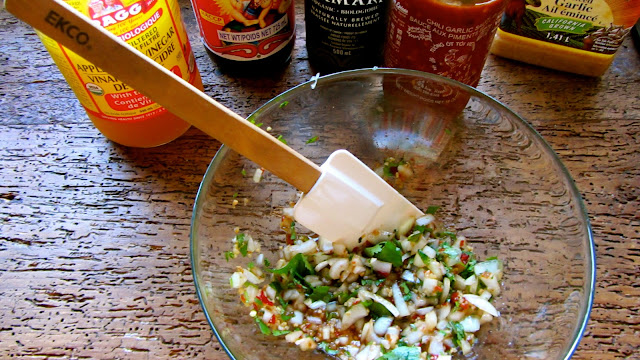 glass bowl with spatula mixing spices and sauce with bottles of sauces in the background