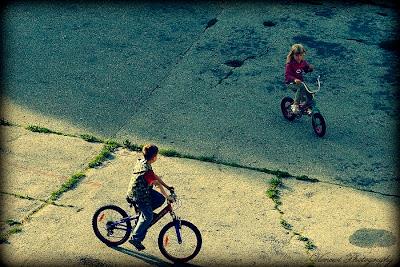 Zdjęcie wykonane z okna, z żyrafiej perspektywy, dzieci na rowerach, kompozycja