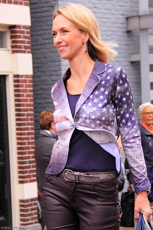 Blond dutch woman wearing her denim jacket with lion prints and leather pants in the street. Street style fashion.